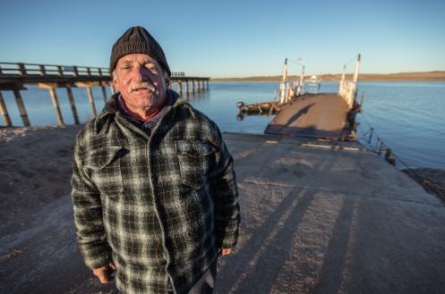 Anselmo maneja la pequeña barca que cruza el lago Garzón para seguir la carretera hacia el noreste.