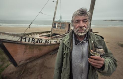 Eduardo Dineigri fue pescado artesanal y carpintero de barcos en Punta del Diablo. hoy esta retirado, como el barco a sus espaldas.