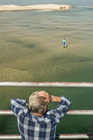 Mientras un hombre esta en el agua con la red, desde el puente, la voz de la experiencia le dirige para  dar con la presa.