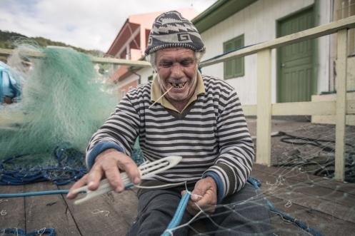 Arreglar las redes lleva mucho tiempo. Con el palo de la boca miden la distancia exacta entre cada nudo.