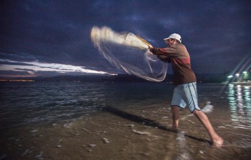 Xexeo lanzando la red de mano desde la playa.