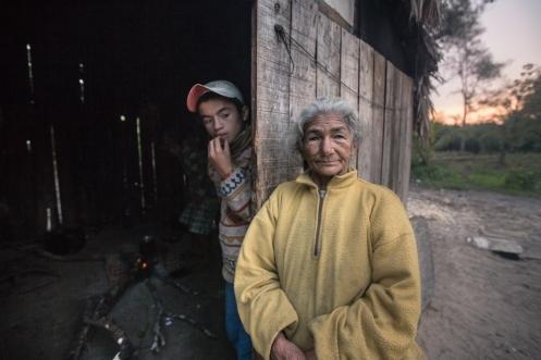 La abuela junto a otro nieto frente al cuarto de hacer fuego. No siempre disponen de gas.