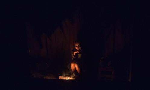 La única de las hermanas se calienta al fuego durante la noche.