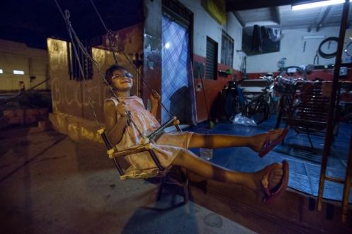 Onieli se balancea en el columpio que su padre Fabio le hizo con palos de escoba viejos.