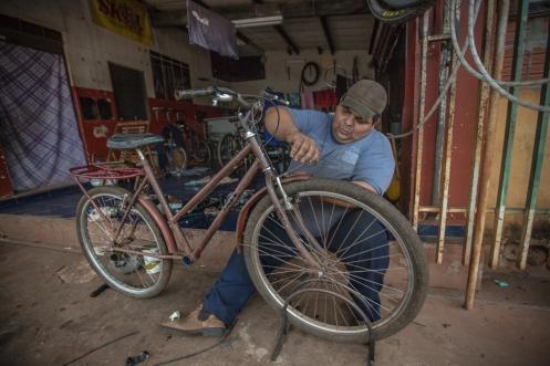 Fabio repara la bicicleta de un vecino