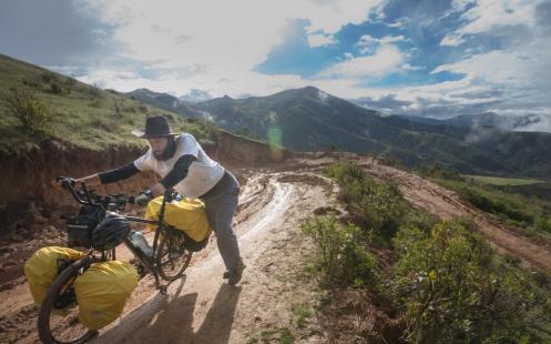 Federico empuja su bicicleta por el barro en uno de los desvíos de la carretera que se encuentra en construcción.