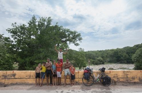Un grupo de niños se lanza al agua desde lo alto de un puente.