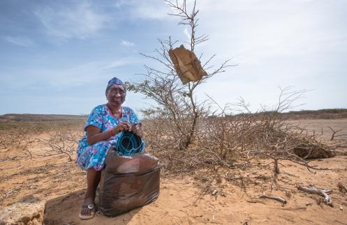 Leticia pertenece a la etnia Wayuu, y mientras teje una mochila espera a algun coche que la lleve al Pilón de Azucar para vender sus artesanias.