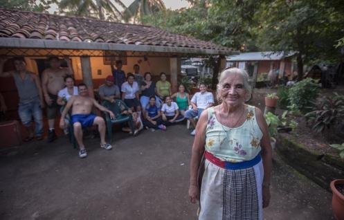 Amanda posa con parte de su familia detrás en su casa.