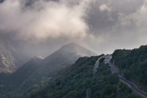 La carretera asciende por las laderas de la montaña hacia las cumbres nevadas.