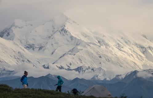 Bea y Alvaro montan la tienda de campaña frente a las inmensas montañas.